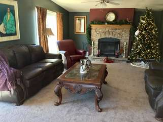 Charming living room with wood burning fireplace has plush seating for relaxing with your favorite companions after a satisfying day in the northern wilderness of Arizona