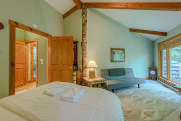 Spacious bedroom with private seating area by picture window