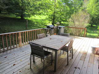 Laurel Chase Back Porch with cedar chairs and outdoor table and lovely surroundings.