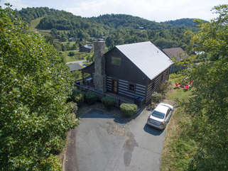 Aerial view looking at parking area and front of home