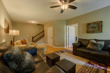 Lower level living area with comfortable seating, gas log fireplace, TV