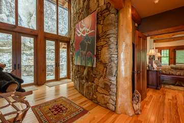 Access to side of home through grand foyer with 2 story stone column