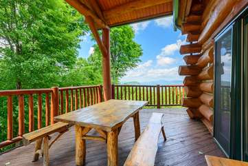 Covered porch and outdoor dining with a view at Spice Mountain Lodge