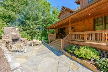 Large stone patio with outdoor fireplace, dining, covered front porch at Valle Crucis Overlook