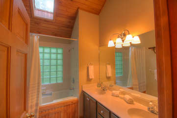 Tuscarora Cottage Large Bathroom with Double Vanity, Jetted Tub and Shower, and Skylight