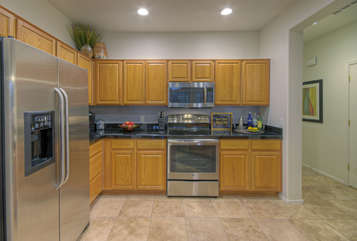 Modern kitchen with stainless steel appliances and granite counters is completely stocked with culinary tools and gadgets