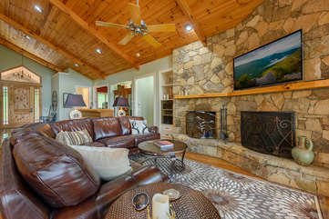 Linville Ridge Retreat living area with dual wood-burning fireplaces, leather couch, TV