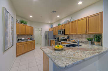 Granite counter tops and stainless steel appliances make kitchen a delightful place to concoct your favorite cuisine