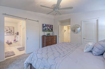 Elegant master suite with king bed has television, ceiling fan and walk-in closet