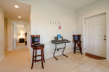 Stand-up Keyboard and Extra Seating beside Lower Level Side Exterior Door in Downstairs Family Room