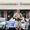 "A man holding a rifle stands in front of the armed forces recruiting center in Winchester, Va., Friday, July 17, 2015.  The man stated that he was there ""to protect the troops.""   Security at military recruiting and reserve centers will be reviewed in the aftermath of a deadly shooting in Tennessee. (Scott Mason/The Winchester Star via AP) MANDATORY CREDIT"
