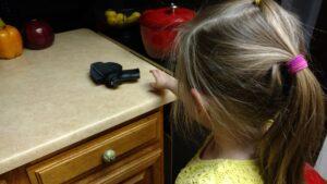 kid reaching for gun