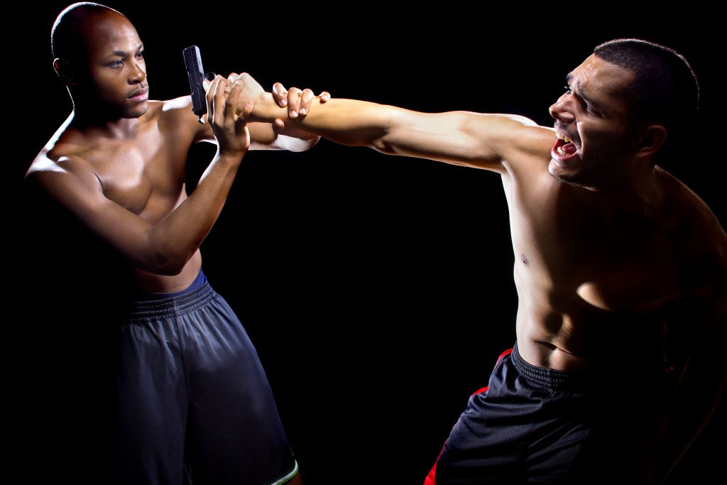 Martial artist disarming a criminal with a gun or close quarter combat
