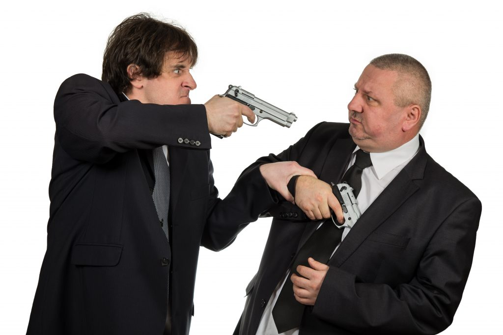 Man with gun threatening woman on white background