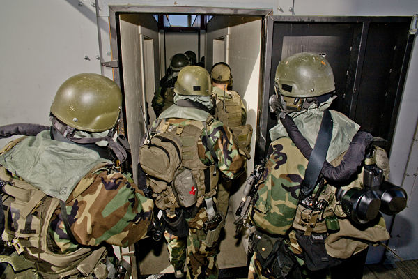 "FBI SWAT (Special Weapons and Tactics) team members wearing specialized ""Weapons of Mass Destruction"" equipment carry M-4 Assault Rifles during a practice session entering or ""breaching"" a room at a ""Live Fire Kill House"" tactical training facility in Southern California. The SWAT team practices five days per month."