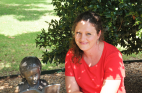 Allison Hurst, psychology alumna, smiles in the shade of a tree.