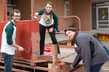 A photo of three students engaging in volunteer work.