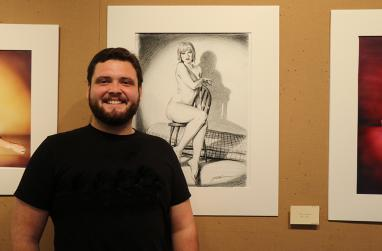 Picture of Dylan Gerber in front of one of his pieces of art.