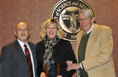 Dr. Michael Nealeigh and President John Feaver present McCasland executive director Barbara Braught with an award.