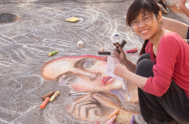 An artist smiles at the camera during USAO's chalk artist festival in 2014