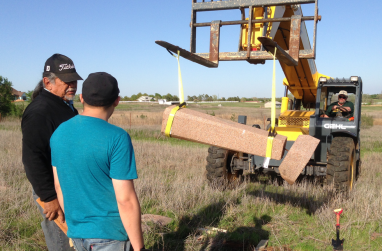 Jesús Moroles speaks with a student as a faculty member handles a giant piece of granite with a forklift.