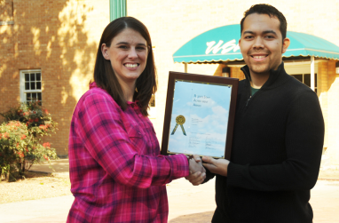 Ashley Donald awards Roland Nunez with the staff achievement award