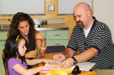 A reading tutor talks with a parent about his child's progress.