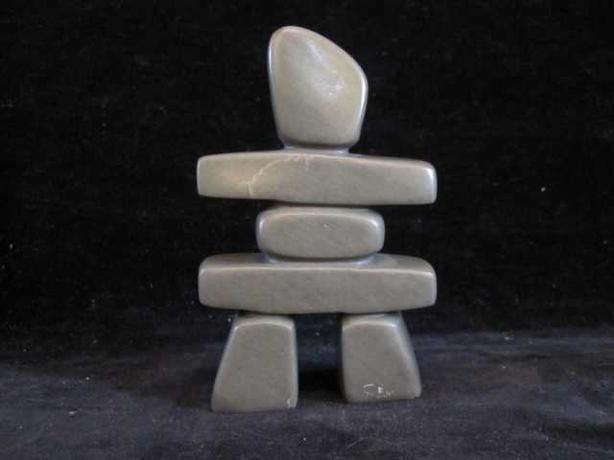 Inuit soapstone carving signed simonie iqaluq depicting
