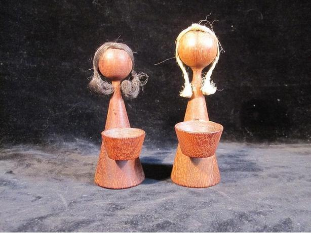 Two teak girl doll figurines with life like hair and baskets.