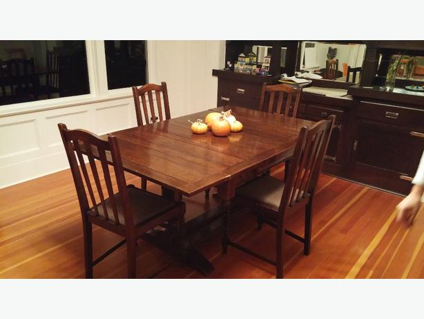 solid dark wood dining table with four matching chairs the chairs