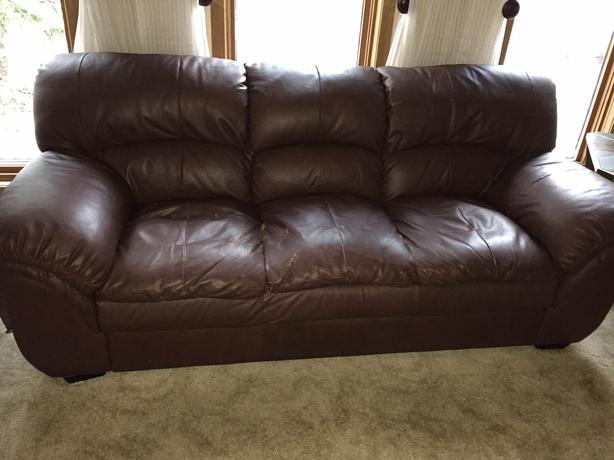 slightly worn bonded leather couch and loveseat along with a glass