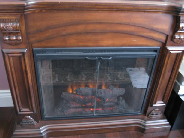 electric fireplace with heater in carved wooden mantle