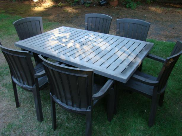 brown resin patio table and six chairs outside comox valley comox