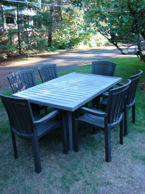 brown resin patio table and six chairs outside comox valley campbell