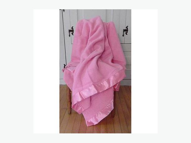 Vintage pink wool blanket with satin-blend binding at top and bottom