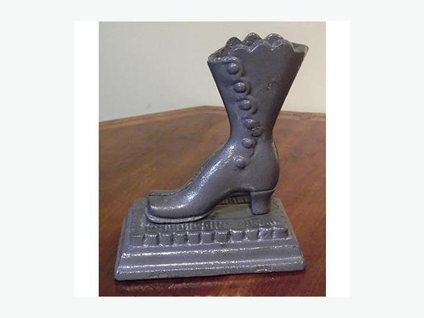 Antique cast iron match safe in the shape of a lady's boot