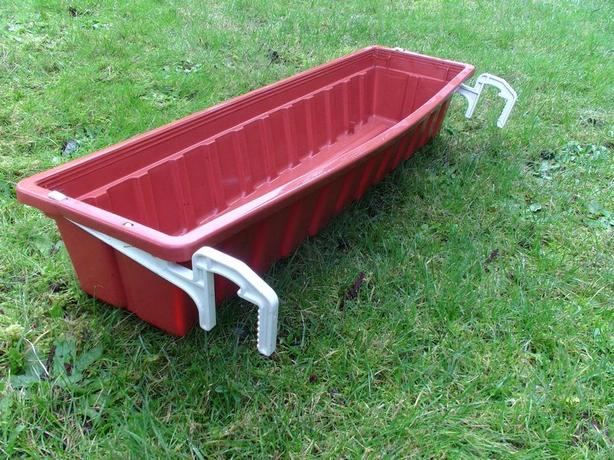 Plastic planter with hanging brackets.