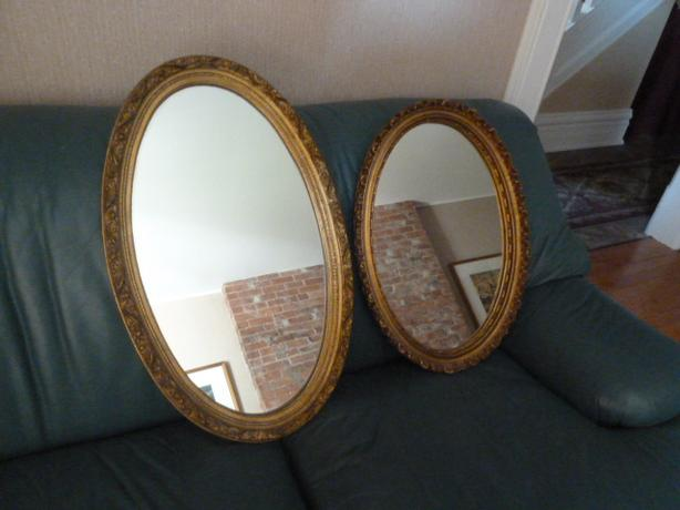 2 oval mirrors with ornate, gold frames.