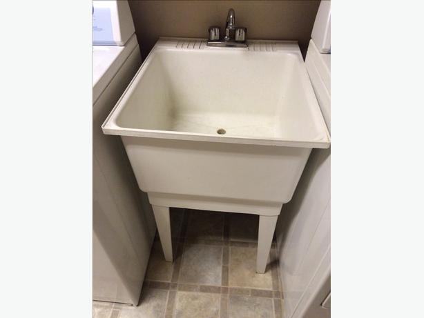 White fibreglass laundry tub, c/w legs and faucet.