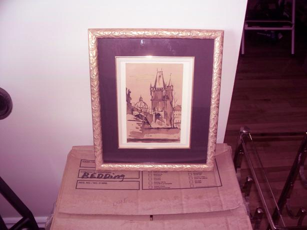gold coloured frame with original print of Prague