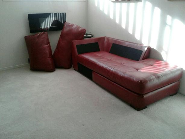 Bonded leather couch. Red. Brand new. Can be used as a bed.