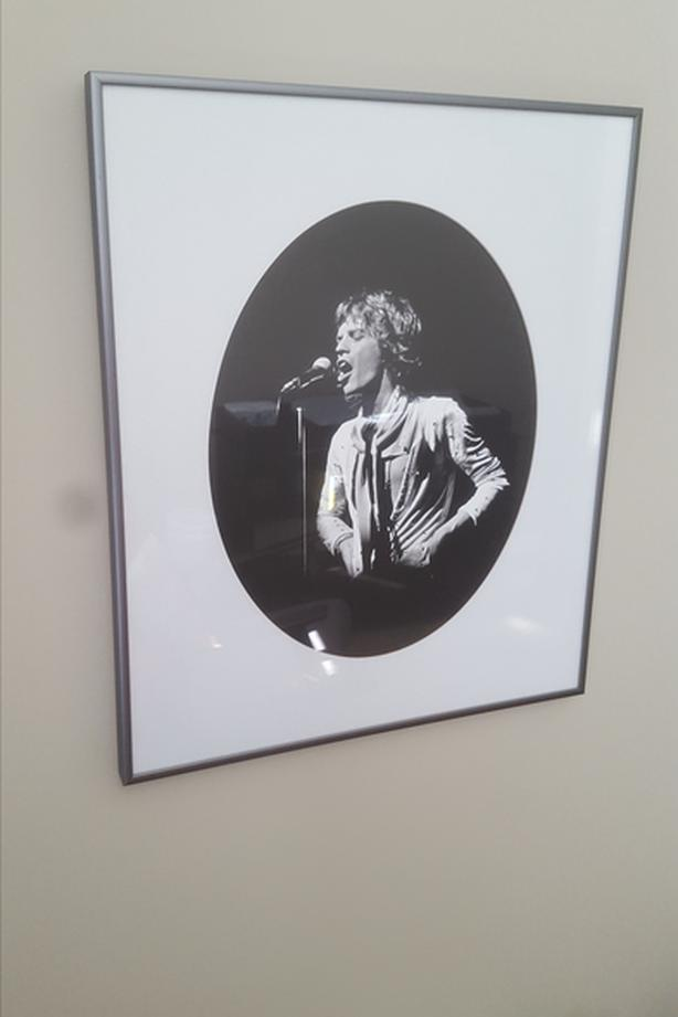 Black and white print of young Mick Jagger singing