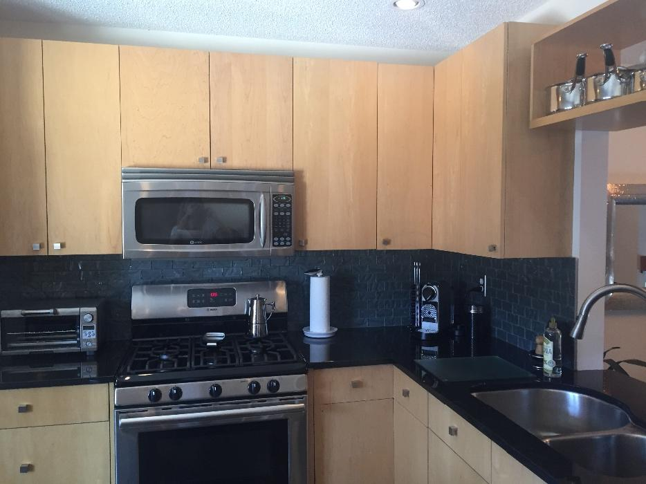 Maple kitchen cabinets and island with black granite ...