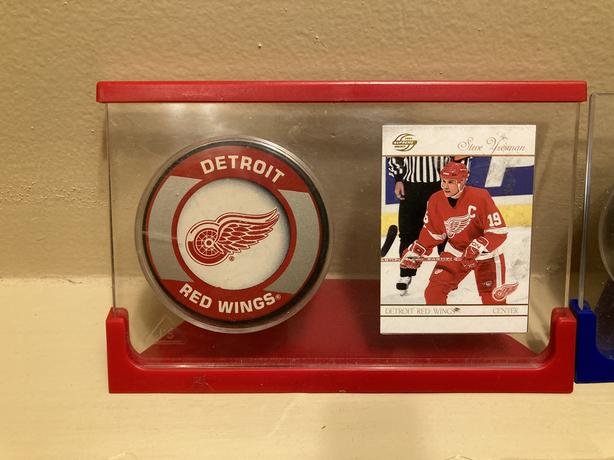 Yzerman and Howe player cards and red wings pucks in stand