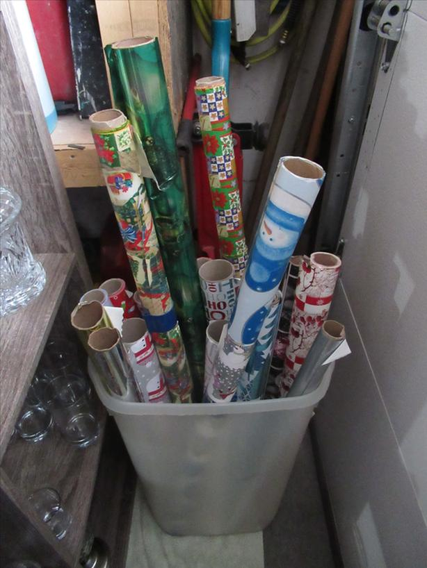 Clear storage bucket with over 15 rolls of partial wrapping paper