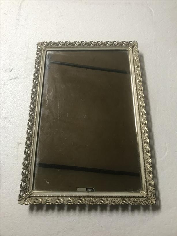 Metal framed serving mirror or maybe hand as a mirror?