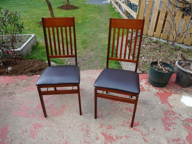 Two folding cherry wood colour chairs with black viny cushions.