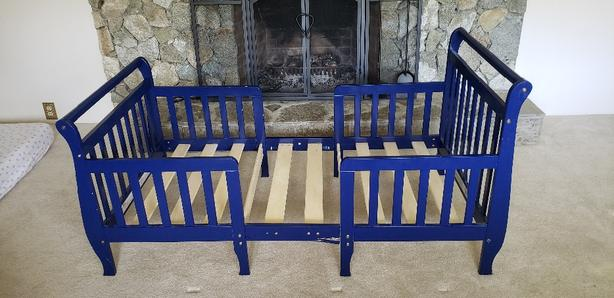 Blue toddler bed with safety rails
