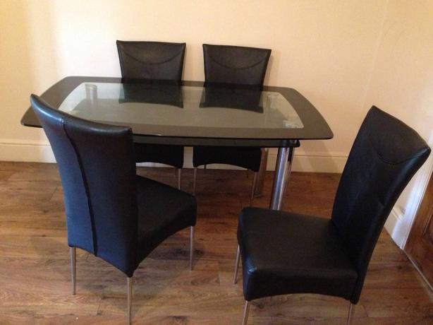large glass table and leather chairs