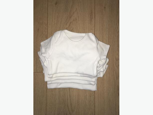 Five white 0-3 vests.